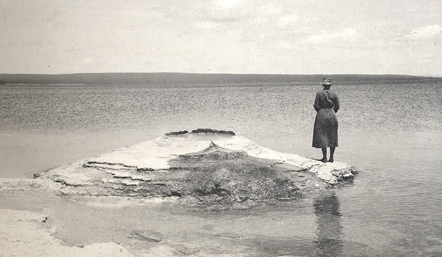 Florence Bascom contemplates Yellowstone Lake from Fishing Rock in 1915.